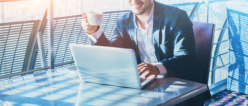 man drinking coffee and sending emails